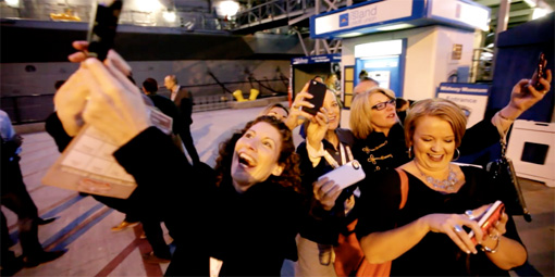 Marketers take selfies outside the U.S.S. Midway aircraft carrier.