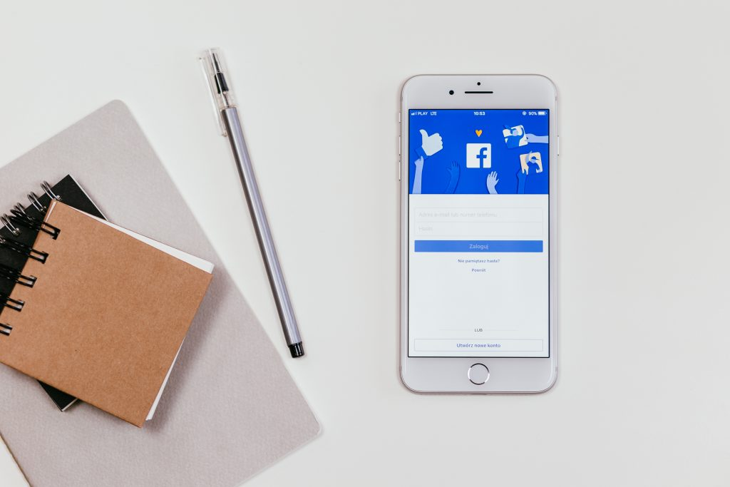 Two notepads, a pen, and a smartphone with the Facebook app open