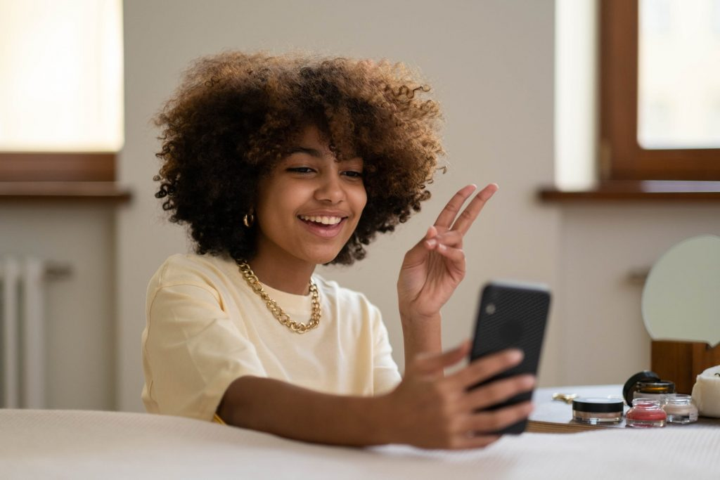 A young black woman smiling as she takes a selfie.