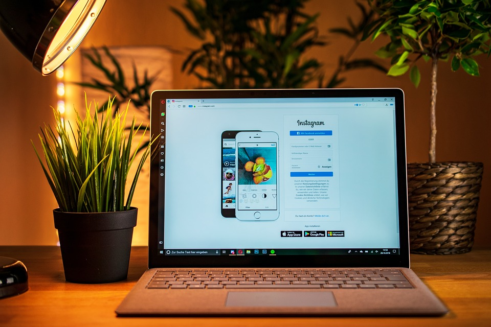 A laptop on a desk under a lamp, showing Instagram's homepage.