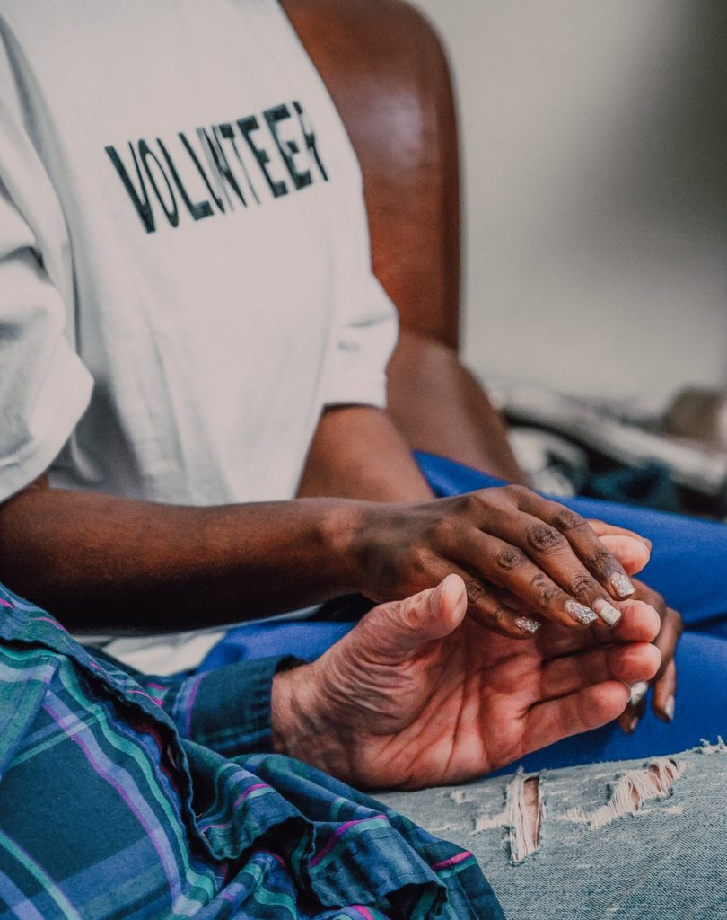 """A person in a shirt that reads """"volunteer"""" holding an elderly person's hand."""